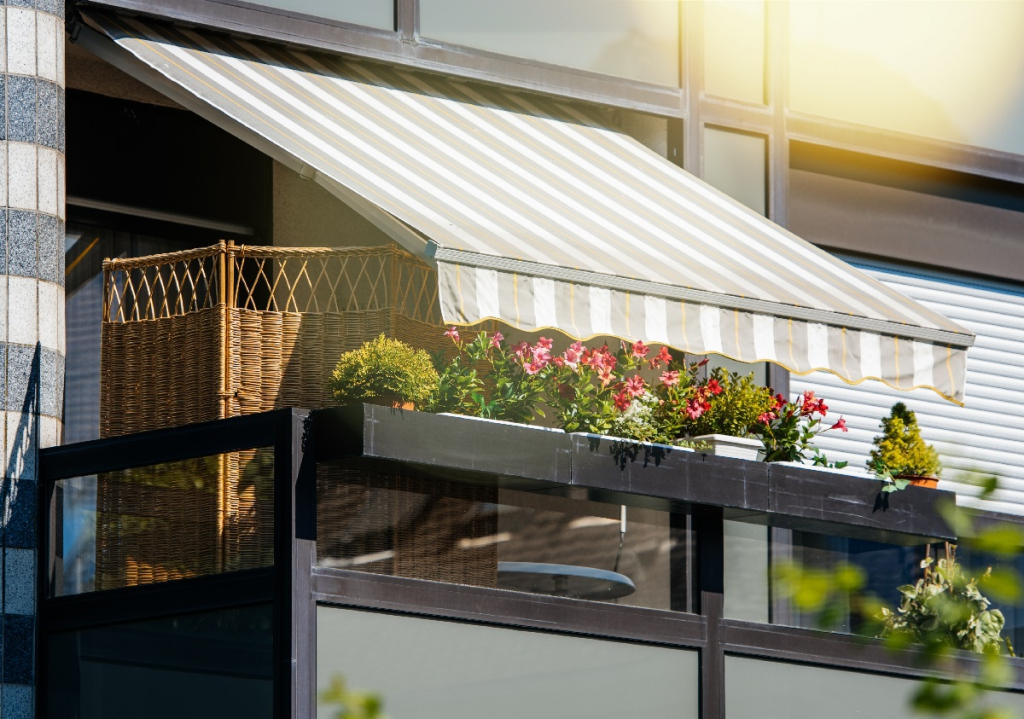 French balcony with beautiful awning and flowers covered with rays of sun - protection during hot weather and radiation